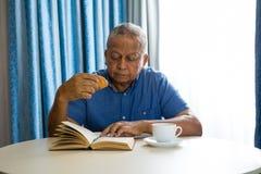 Croissant mangeur d'hommes supérieur tandis que livre de lecture dans la maison de repos Image libre de droits