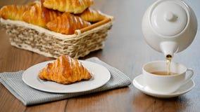 Croissant met thee Het concept van het ontbijt Gietende thee in kop thee stock footage