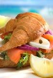Croissant met zalm op het strand Stock Fotografie