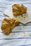 Croissant, miette de pain sur la nappe Photos stock
