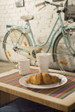 Croissant in a plate, mugs and vintage bicycle in coffee shop interior Royalty Free Stock Images