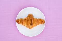 Croissant na białym talerza i menchii tle Zdjęcie Royalty Free