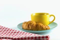 Croissant no prato verde com branco alterno amarelo do vermelho do café e da tela do copo Fotografia de Stock Royalty Free