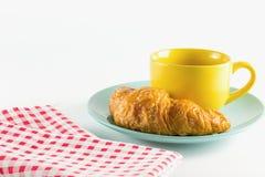 Croissant no prato verde com branco alterno amarelo do vermelho do café e da tela do copo Foto de Stock Royalty Free