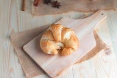Croissant op houten besnoeiingsraad op lijsthout en stof uitgezochte FO Stock Afbeeldingen