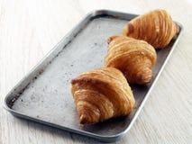 Croissant op roestvrij staaldienblad stock afbeelding