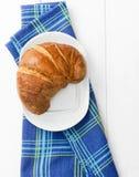 Croissant over bluish cloth Stock Photos