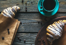 Croissant in a paper bag with a cup of coffee. Breakfast, snack, food Stock Photos