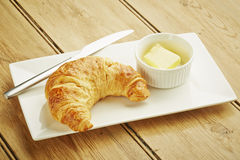 Croissant pastry on white dish. And wooden table top Royalty Free Stock Image