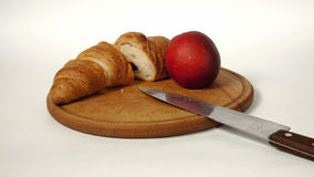 Croissant  and peach on the board Royalty Free Stock Photos