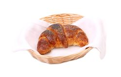 Croissant with poppy on wicker basket. Royalty Free Stock Images
