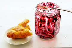 Croissant and  pot of jam over white Royalty Free Stock Photos