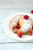 Croissant with raspberries on a white plate. Food closeup Stock Photos