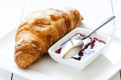Croissant with raspberry jem. On white table Royalty Free Stock Images