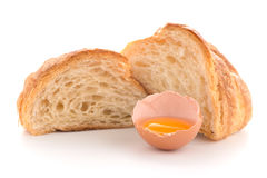 Croissant and raw egg. Fresh croissant and raw egg on white background Stock Images