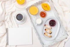 Croissant recentemente cozido, suco de laranja, doce, copo do café preto na bandeja de madeira branca na manta Bolinho caseiro Pa Fotografia de Stock Royalty Free