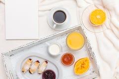 Croissant recentemente cozido, suco de laranja, doce, copo do café preto na bandeja de madeira branca na manta Bolinho caseiro Pa Imagem de Stock Royalty Free