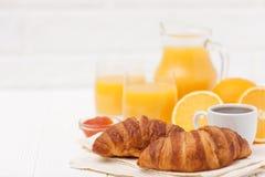 Croissant recentemente cozido, suco de laranja, frutos frescos, xícara de café no fundo de madeira branco Café da manhã do francê Imagens de Stock
