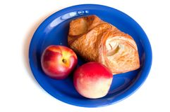 Croissant and red peaches on the blue plate Royalty Free Stock Images