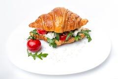 Croissant saboroso com tomate e ruccola na placa do whie imagem de stock