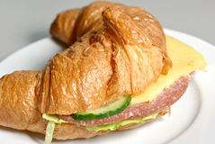 Croissant with salad, cucumber, cheese and salami. On a white plate Royalty Free Stock Photo
