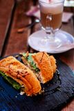 Croissant with salmon and a glass with latte for breakfast. Royalty Free Stock Images
