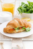 Croissant with salted salmon and arugula, closeup, vertical Royalty Free Stock Photos