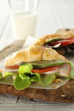 Croissant sandwich. Fast food but healthy ingredient such as cucumber, tomato, green salad, ham and milk Royalty Free Stock Image