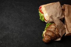Croissant sandwich on black background. Morning breakfast or snack when hungry. Street food. Copy space for text royalty free stock photo