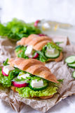 Croissant sandwich with cheese and vegetables for healthy snack, craft paper and greens background. Picnic summer food. Selective Stock Image