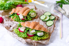 Croissant sandwich with cheese and vegetables for healthy snack, craft paper and greens background. Picnic summer food. Selective Royalty Free Stock Images