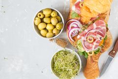 Croissant sandwich with ham, olives and vegetable. S on a wooden board Royalty Free Stock Image