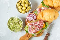 Croissant sandwich with ham, olives and vegetable. S on a wooden board Stock Photo