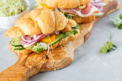 Croissant sandwich with ham, olives and vegetable. S on a wooden board Royalty Free Stock Photography