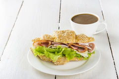 Croissant sandwich with lettuce, bacon, cheese on white plate and cup of coffee on a wooden background Royalty Free Stock Photography