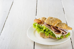 Croissant sandwich with lettuce, bacon, cheese on a white plate. And a wooden background Royalty Free Stock Photos