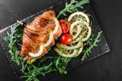 Croissant sandwich with red fish, avocado, fresh vegetables and arugula on black shale board over black stone background. Healthy food concept stock photos