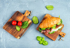 Croissant sandwich with smoked meat Prosciutto di Parma, sun dried tomatoes, fresh spinach and basil on small rustic Royalty Free Stock Image