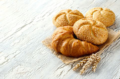 Croissant and small loaf with sesame, ears of wheat, baked bread Royalty Free Stock Photography