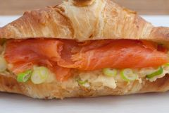 Croissant with smoked salmon and scrambled eggs Stock Photo