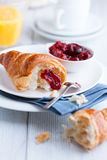 Croissant and sour cherry jam on a white plates Stock Photography