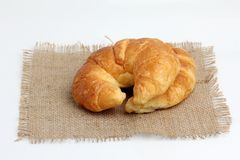 Croissant on spuare frayed burlap Royalty Free Stock Images