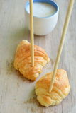 Croissant stab chopstick walk to hot latte coffee cup Royalty Free Stock Photo