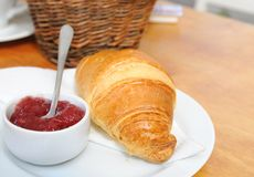 Croissant and strawberry jam on plate Stock Photos