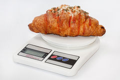 Croissant stuffed with pizza on the kitchen scale Stock Photography