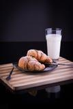Croissant su un piatto con zucchero e bicchiere di latte in polvere Fotografia Stock