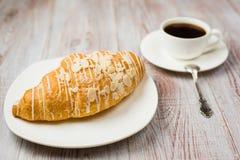 Croissant su un piatto e su una tazza con la bevanda immagini stock libere da diritti