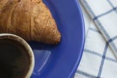 Croissant sul piatto blu e sul caffè nero Immagini Stock Libere da Diritti