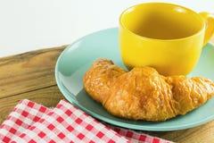 Croissant sul piatto verde con bianco alternante giallo di rosso del caffè e del tessuto della tazza Fotografia Stock