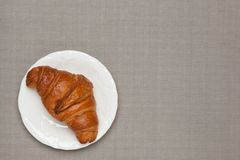 Croissant on the table cloth Stock Photos